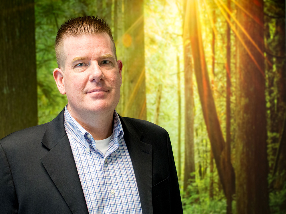headshot of Mark Forward standing infront of a decorative wall in the office