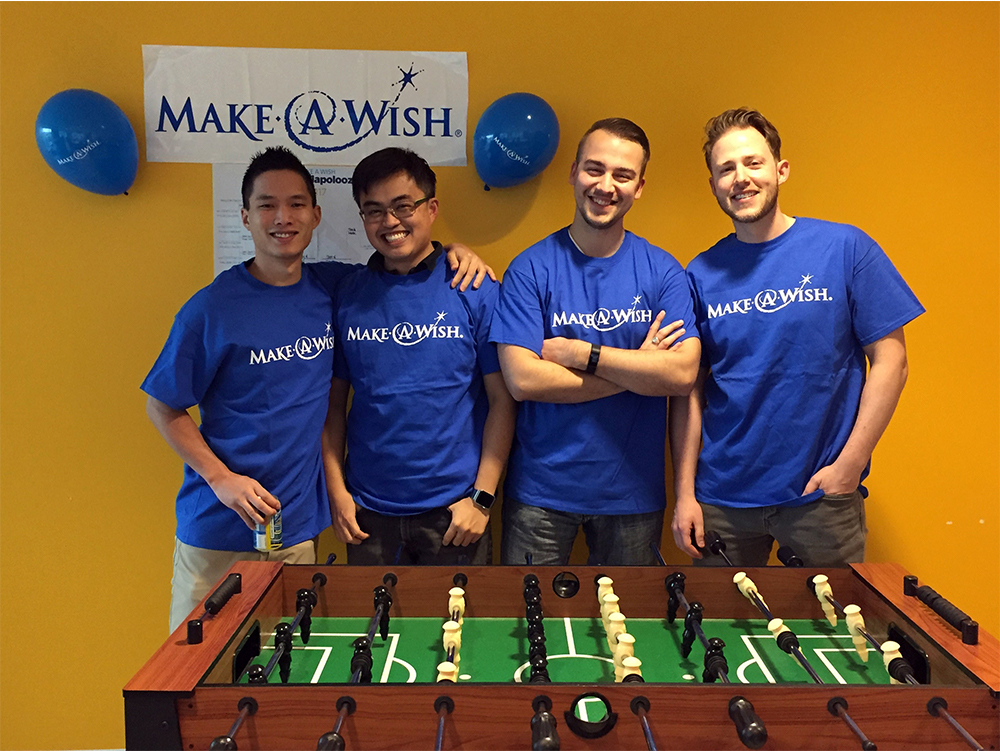 Four employees wearing make-a-wish-t-shirts are standing behind a foosball table