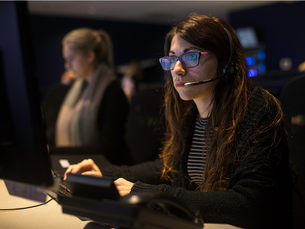 A women wearing a headset and answering the phone while working in a operations centre