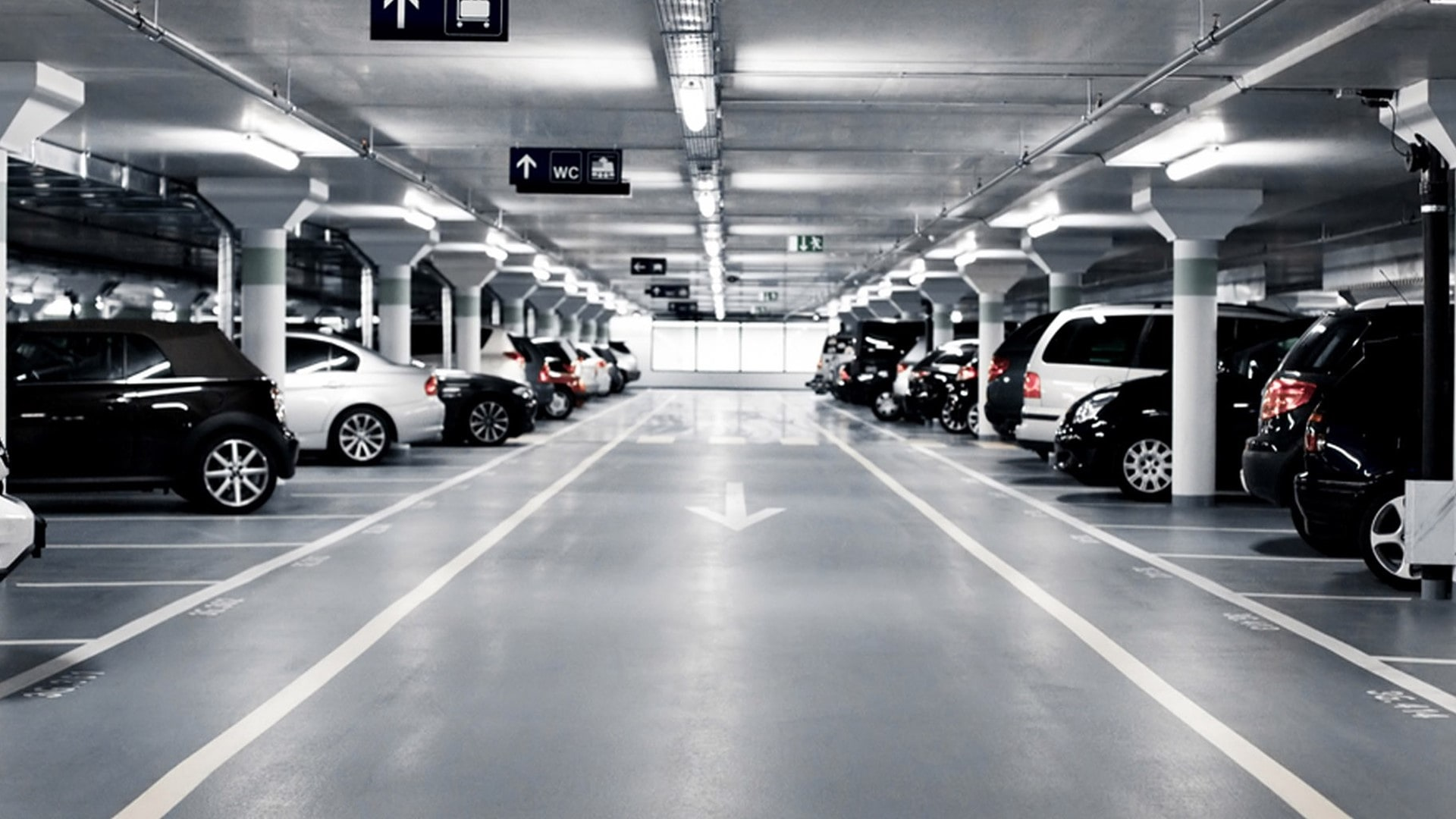 a dark parking lot with cars parked on the left and right side