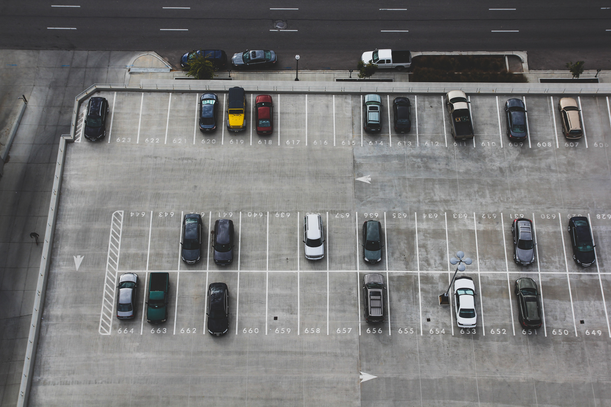 An ariel image of an outdoor parking lot with some cars parked in the stalls